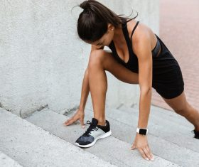 Portrait of a fitness woman doing sports exercises on stairs outdoors