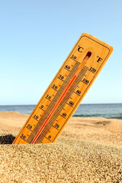 A selective focus shot of a thermometer in the beach sand with a blurred background
