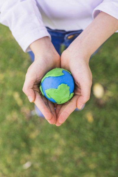 elevated-view-small-clay-globe-cupped-hands-grass