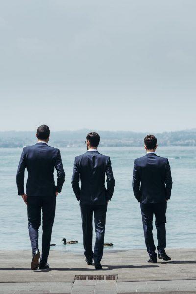 Five men in classy suits walk towards the blue sea