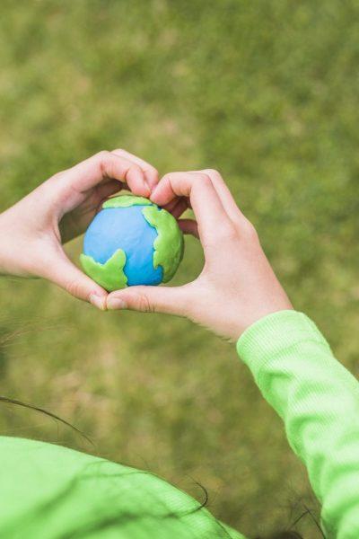 heart-shape-hands-surrounds-colorful-plasticine-planet