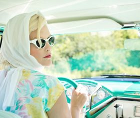 woman-driving-vintage-car-on-road-during-daytime-33678